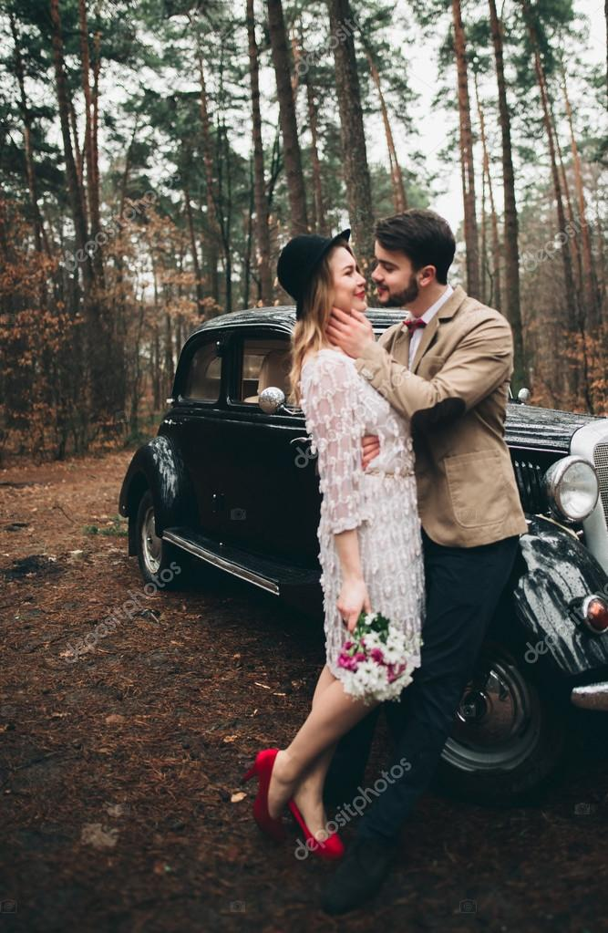 Stylish Loving wedding couple kissing and hugging in a pine forest near retro car