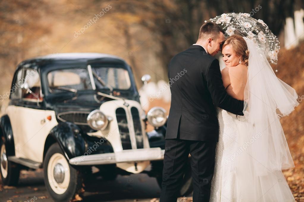 Stylish wedding couple, bride, groom kissing and hugging near ...
