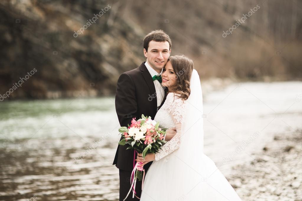 Beautifull wedding couple kissing and embracing near river with stones