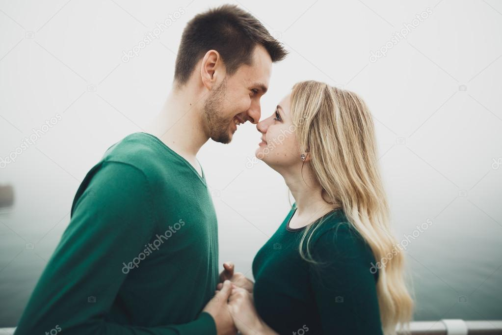 lovely couple kissing and hugging on a sea dock stock photo