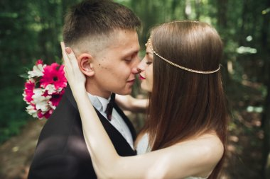 Beautiful young wedding couple is kissing and smiling in the park