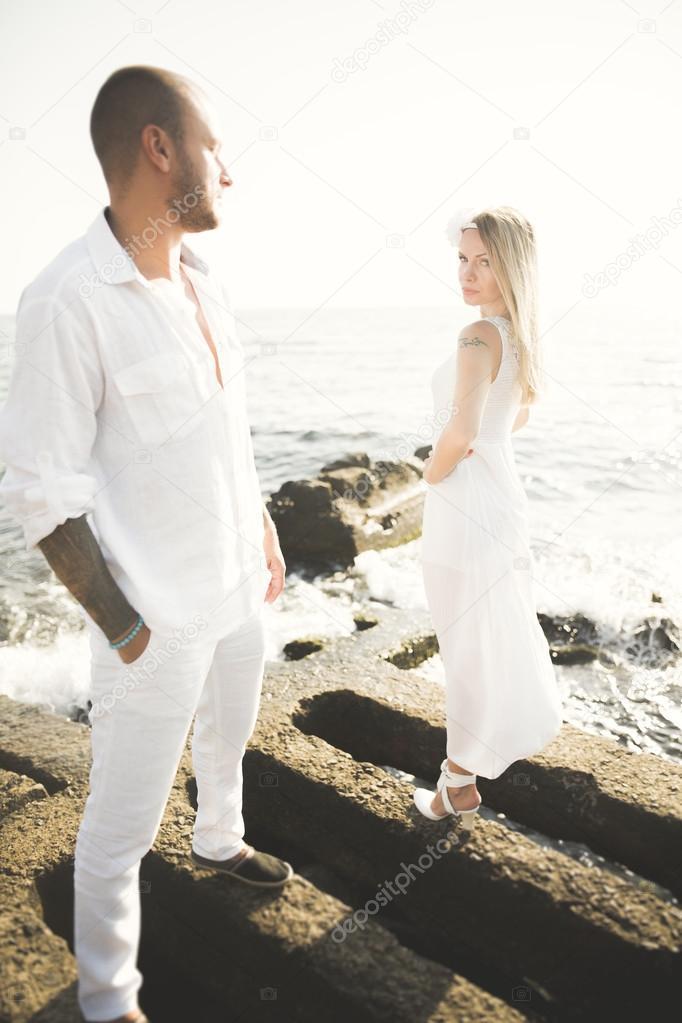 Romantic loving couple posing on stones near sea, blue sky