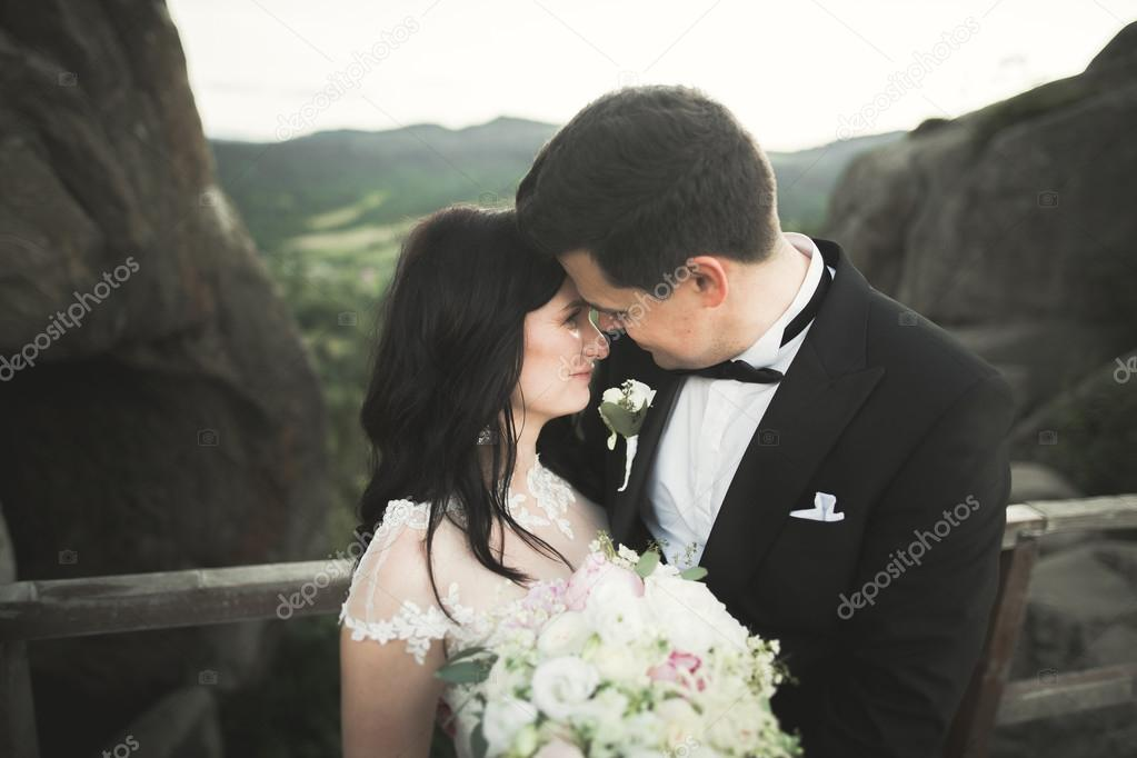 Gorgeous bride, groom kissing and hugging near the cliffs with stunning views