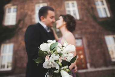 Wedding flowers bouquet with newlywed couple on background
