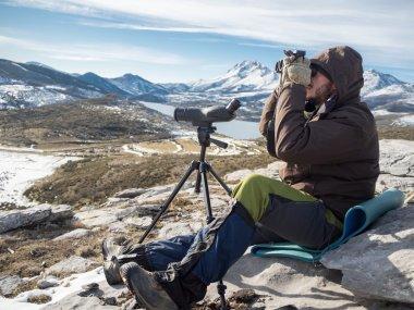 Man in the mountains looking through binoculars under blue sky