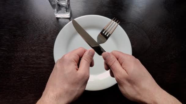 muž držící vidličku s nožem u stolu