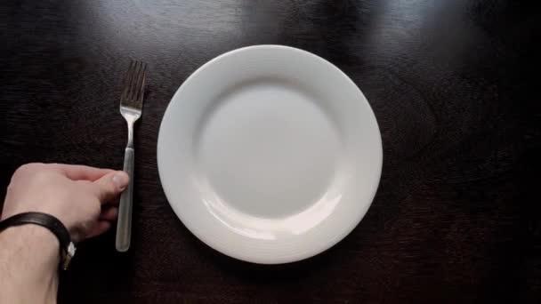 příbory jsou umístěny na dřevěném kuchyňském stole na talíř