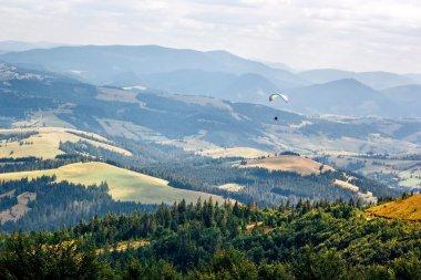 Paraglider flying against beautiful mountains landscape. Carpathian, Ukraine.