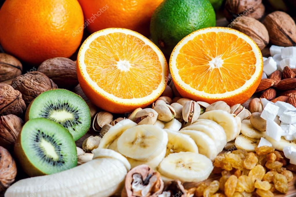 Fresh fruits. Healthy food. Mixed fruits and nuts background.Healthy  eating, dieting, love fruits. Studio photography of different fruits and  nuts on old wooden table. Organic Healthy Assorted Fruits. — Stock Photo ©