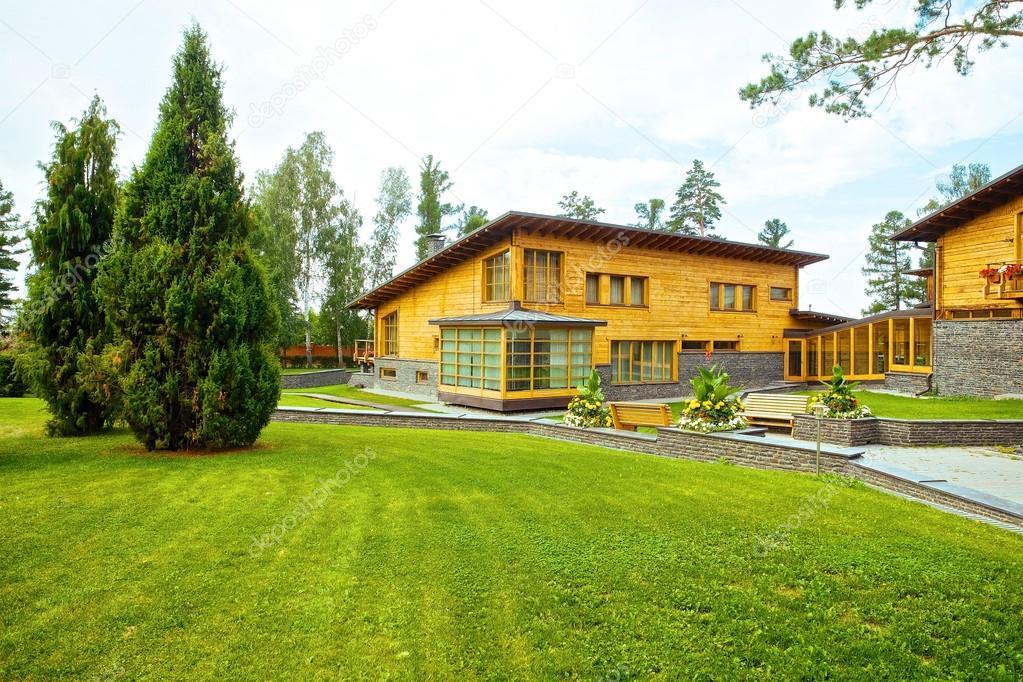Gevel van een prachtige houten huis met groene tuin u redactionele