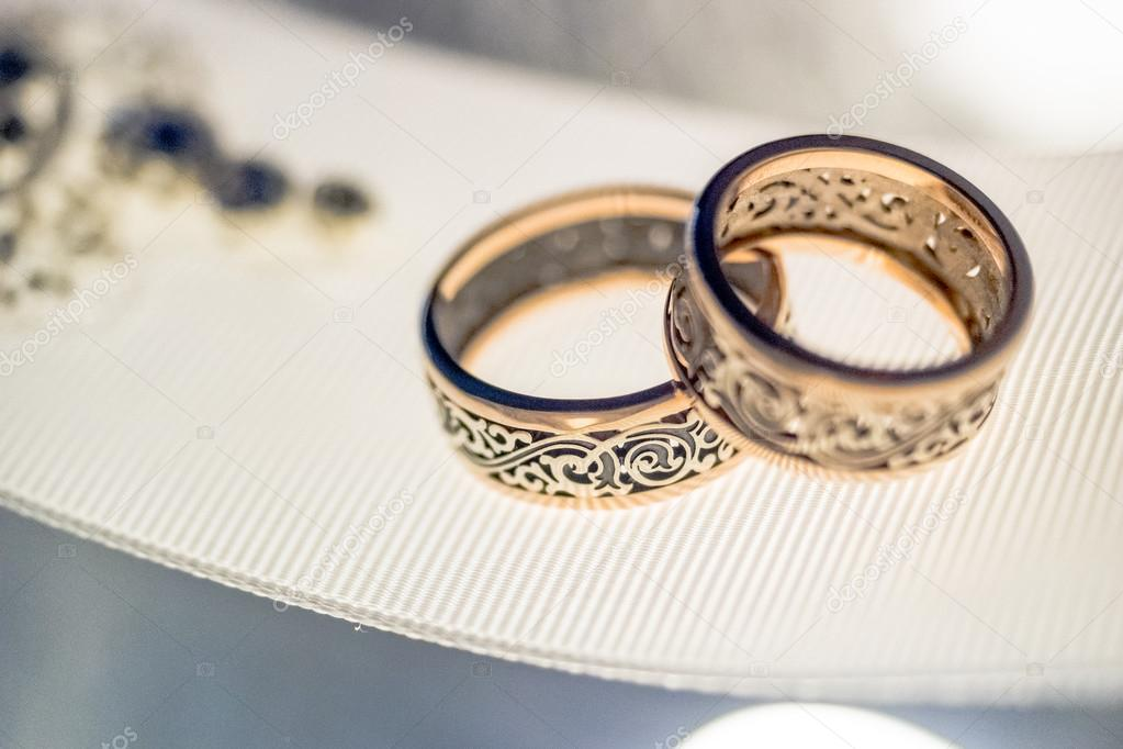 Two wedding rings with rare design on white broad ribbon Stock