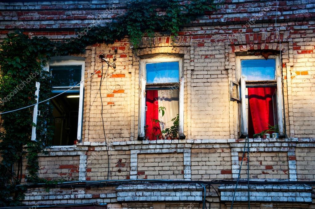 three open windows on brick building in the evening