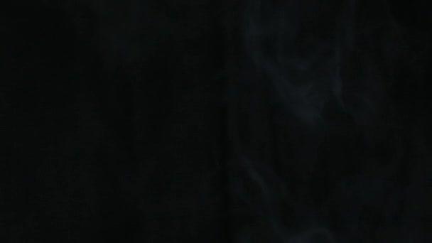 Rauch Wolke über schwarzen Hintergrund kommen vom rechten Rand und schieben nach links unten, Full Hd 25p