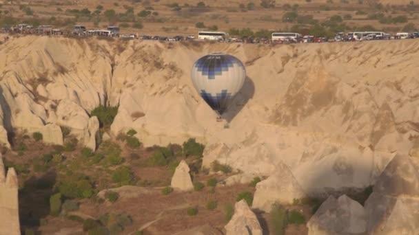 Hot air balloon with blue white envelope hangs near cliff