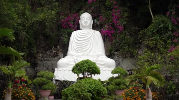 Amazing statue of calm Buddha among plants and flowers