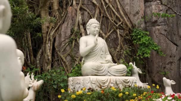 Bílé sochy Buddhy s jeleny a studenty v blízkosti chrámu
