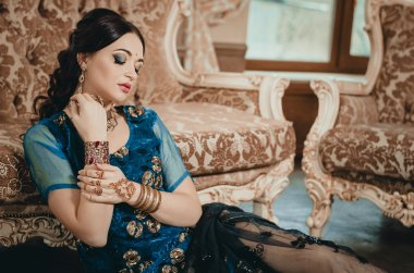 beautiful woman in a traditional Chinese outfit Indian blue, sitting on the floor in a luxury sofa. On her hands painted with henna mehendi
