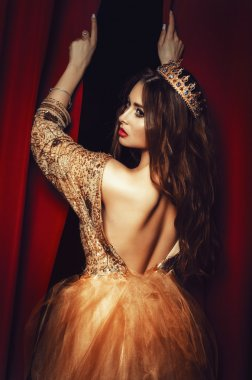 beautiful young brunette woman in a yellow dress lush, with a crown on his head is back on a background of red curtains