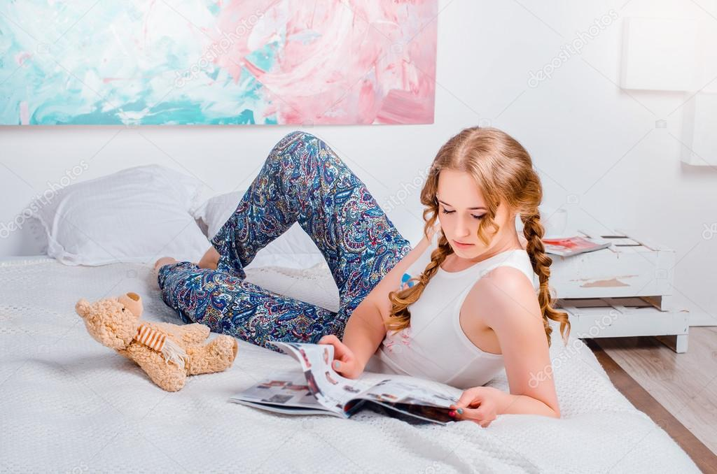 d4adc42fd2d0de Cute young girl with two braids, at home wearing pajamas, lying on the bed,  with her soft toy bear, she reads a magazine and smiling — Photo by ...
