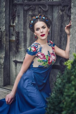 portrait of a beautiful young brunette in a blue dress, a wreath on his head, blue eyes and red lips against the background of an old wooden door. Deuvshka Ukrainian, Russian girl