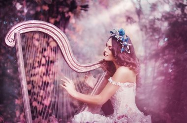 beautiful brown-haired woman with a flower wreath on her head, wearing a white dress playing the harp in the forest