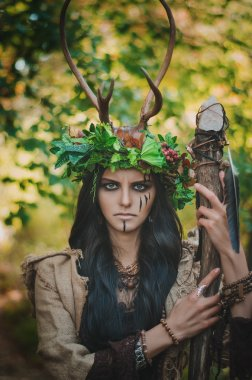 Portrait of a brunette with a floral wreath on her head, horns and wooden stick in hand, in the forest