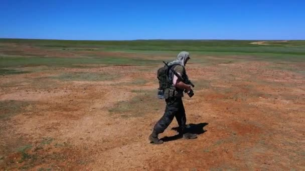 Slow motion - tired soldier-sniper walks across the scorching desert land. The concept of military conflicts and survival in extreme conditions.