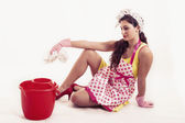Fotografie pretty housemaid with cloth and bucket cleaning the floor