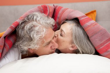Closeup of a mature couple relaxing in bed at home