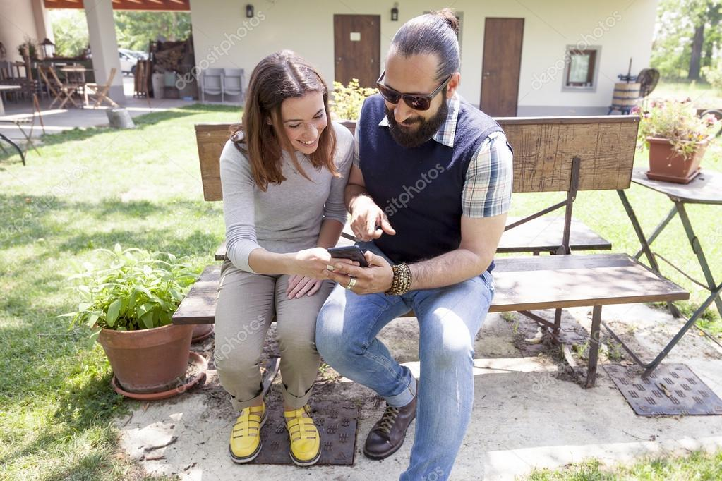 young couple of lovers consults smart phone outdoor