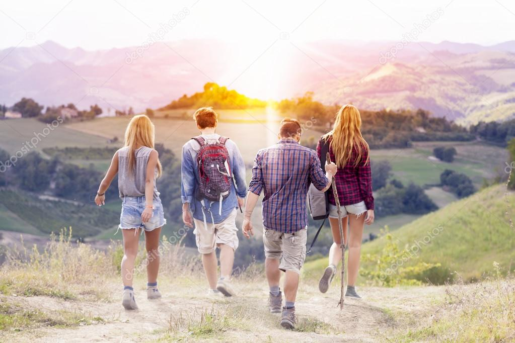 group of young hikers walking toward the horizon over the mounta