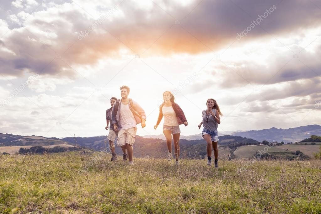group of young hikers running toward the horizon over the mounta
