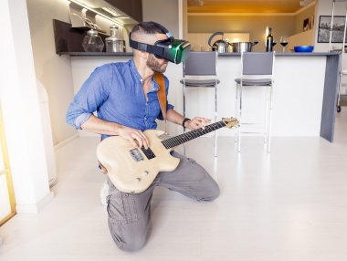 young adult playing guitar at home using viewer for virtual real