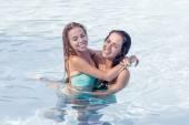 Pretty girls play and hug in pool