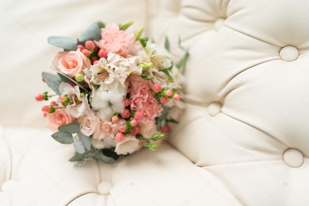 Bridal bouquet on leather sofa — Stock Photo © alexnope #109523142