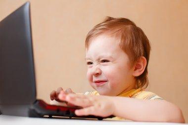 little smart boy surfing the Internet on laptop