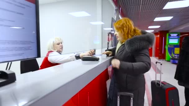 Woman Middle Age With a Bag Buying a Ticket at Red the Box Office and the  Cashier Show Direction Railway Airport ⬇ Video by © elingerrr88.gmail.com  Stock Footage #102004058