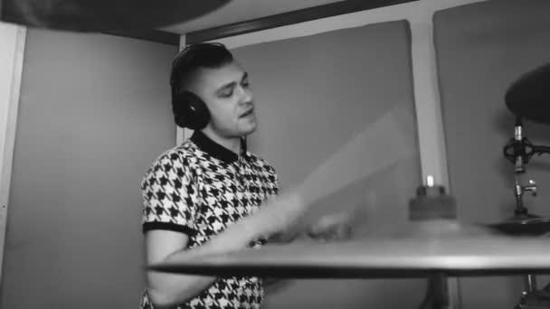 Fiatal dobos, a fejhallgató, a stúdióban. Hang regisztráló készülék. Fekete-fehér. Vértes