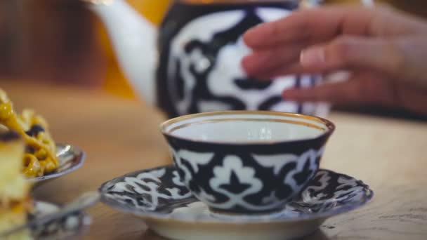 Sype z konvici do šálku. Nádobí pro čaj. Krásné nádobí. Kantýna