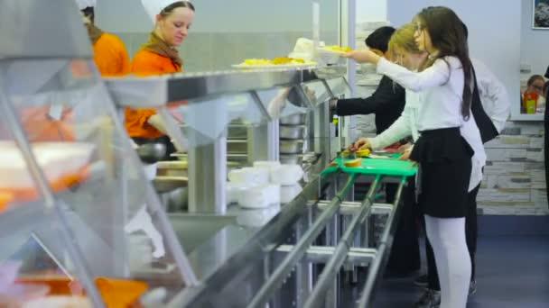 Studenti v jídelně. Kantýna. Distribuce potravin. Linka pro potraviny. Vzdělávací téma