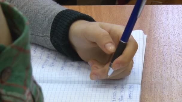 Fiú kezében tartja a toll és az asztalon pihen. Írás jegyzetfüzet. Vértes. Gyermekek, Scool, oktatás