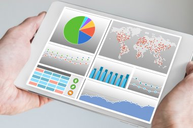 Hand holding modern tablet or mobile device with analytics dashboard for sales, marketing, accounting,