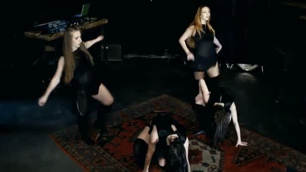 zeitgenössische Tanzperformance von vier Tänzern auf dunklem Boden
