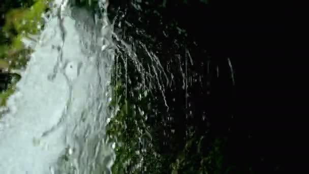 Zobrazit pod vodopád splash na kamenech v lese mezi horami.