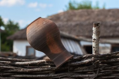 Old clay Jug on a wicker fence, rustic style, rural scenery