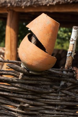 Old broken clay pot close up at wattle fence. Rural scene.