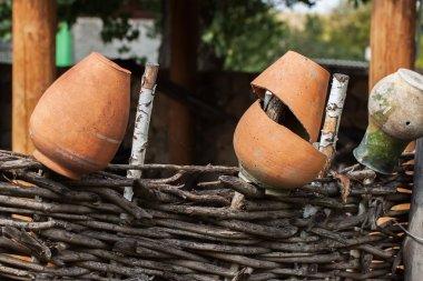 Village, rustic wattle fence, old clay pots . Rural scene