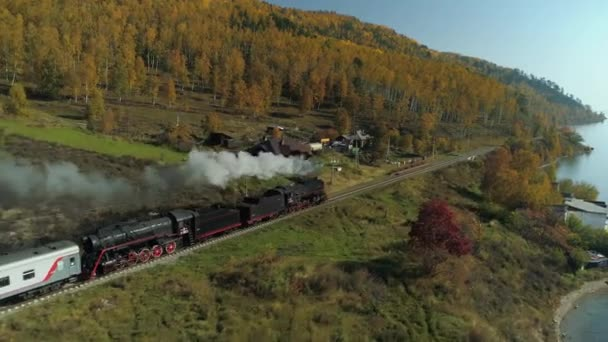 Aerial follow train steam locomotive engine travels across beautiful Trans-Siberian Railway old wooden village. Baikal autumn yellow forest best Russia village. Smoke from the chimney. Sunny day