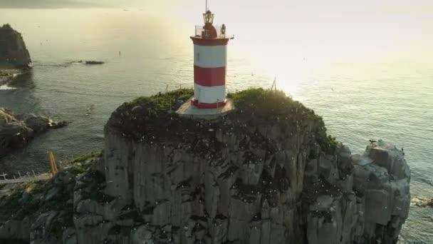 Vzduch kolem romantického majáku Basargin na ostrově Vladivostok. Pomerančové slunce zapadá. Emocionální ptáci, racci, hejna mušek. Stará historická památka. Silné mořské pobřežní vlny. Léto
