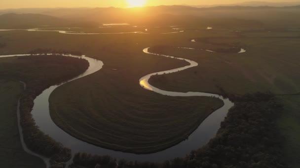 Vrtulník nad epickou přírodní krajinou. Kinematografický oranžový horizont zapadajícího slunce. Serpantinská řeka protéká sluncem zalitým polem. Vladivostok Dálný východ nejlepší scenérie. Pozadí hor. Zlatá hodina